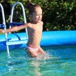 Cute four-year old girl jumping into a swimming poo — Stockfoto