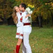 Young couple in Ukrainian style clothes outdoors — Stock Photo
