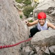 Portrait of cheerful female climber ascending a rock — Stock Photo
