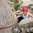 Stock Photo: Portrait of cheerful female climber ascending rock