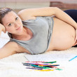 Foto Stock: Pretty young pregnant womdrawing with pencils