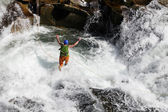Young man rope jumping in rapid waters of a mountainous river — Stock Photo