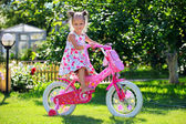 Portrait of a cute four-year old girl riding her bicycle — Stock Photo