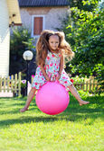 Cute four-year girl bouncing on a big ball outdoors — Stock Photo