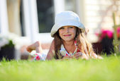 Cute four-year girl lying on the grass outside — Stock Photo