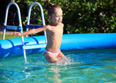Cute four-year old girl jumping into a swimming poo — Stock Photo