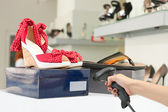 Cropped view of shop assistant scanning code on shoe box — Stock Photo