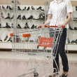 Young attractive woman with a shopping cart in a shoe store — Stock Photo