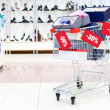 Shopping cart full of shoe boxes in a shoe department with added images of discount tags — Foto Stock
