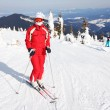 Female skier standing on mountain slope — Stock Photo
