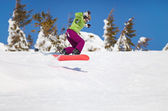 Female snowboarder jumping on mountain slope — Stock Photo