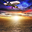 Jet plane over the sea at sunset time — Stock Photo