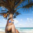 Young woman sitting on the palm tree — Stock Photo