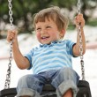 Little boy having fun on chain swing - Stock Photo