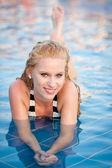 Attraktiv blond tjej i bikini badkläder i poolen på sen sommareftermiddag — 图库照片