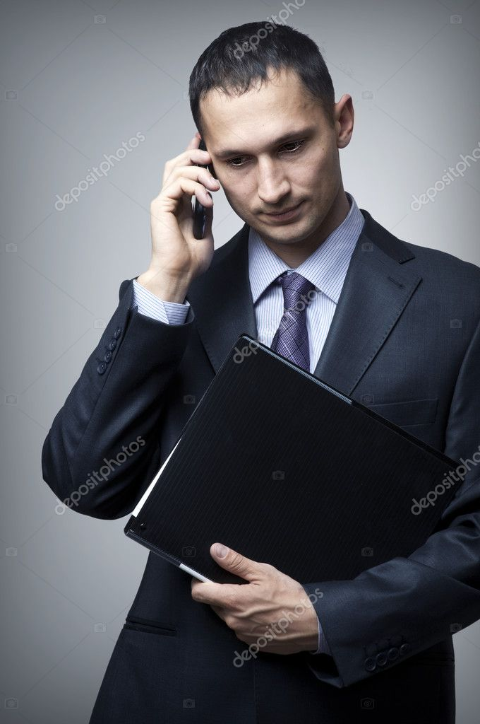 Young business man with cell phone and black folder  Stock Photo #10893256