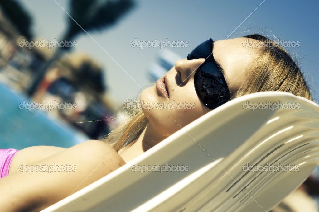 Beautiful woman lying on a deckchair at the beach  Stock Photo #11426310