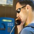 Handsome man in telephone box — Stock Photo #11459216