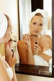 Young woman putting mascara on — Stock Photo