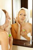 Young beautiful woman applying lotion — Stock Photo