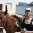 Young man with horse outdoor — Stock Photo