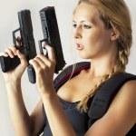 Woman holding two hand gun — Stock Photo #11572269