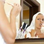 Woman in bathroom brushing teeth — Stock Photo