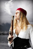 Girl pirate blows a smoke from a old pistol — Stock Photo