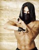 Man assassin with sexy torso in mask — Stock Photo