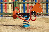 Playground's wooden horse and moto — Stock Photo