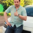 Happy man sitting on new car and looking serious on nature green — Stockfoto