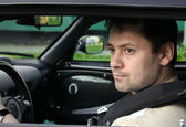 Young man driving car sitting inside and looking from window. Cl — Stock Photo