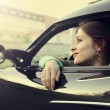 Beautiful smiling girl sitting in new car and looking from windo — Stock Photo #11112365