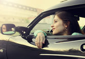 Beautiful smiling girl sitting in new car and looking from windo — Stock Photo