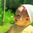Closeup portrait of fun smiling baby girl in hat on green grass — Stock Photo