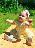 Güneşli yaz b yeşil çimenlerin üzerinde oturan güzel bebek kız — Stok fotoğraf