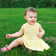 Beautiful happy baby girl sitting on green grass on nature bacgr — Stock Photo #11913764