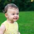 Beautiful fun baby girl smiling on summer green grass background — Stock Photo