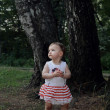 Along lost baby girl walking in forest and looking for family wi — Stock Photo