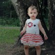 Beautiful lost baby girl in forest near the trees looking with w — Stock Photo