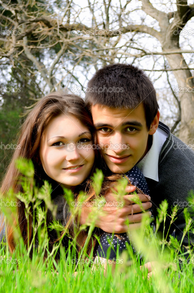 The young guy and the girl lie on a bright green grass in an embrace and smile — Stock Photo #10771528