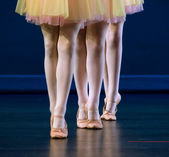 Feet of trio of dancers in flat shoes and yellow and pink skirts — Stock Photo