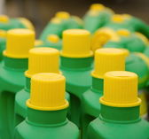 Rows of bright green plastic bottles with yellow caps — Stock Photo