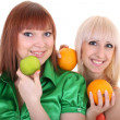 Two young attractive women with green apple and oranges — Stock Photo