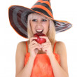 Young attractive woman in hat biting red apple — Stock Photo