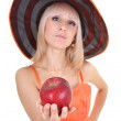 Young attractive woman in hat giving red apple. focus on apple — Stock Photo #11791071
