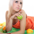 Young attractive blonde with fruits lying — Stock Photo