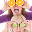 Two funny women with orange and lime slices instead of eyes — Stock Photo #11791118