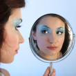 Stock Photo: Beautiful womwith make-up looking at mirror