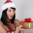 Surprised brunette woman in santa hat with golden gift - Stock Photo